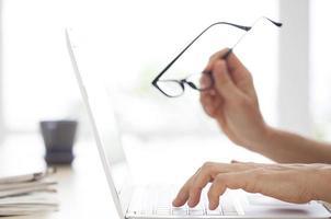 close-up da mulher mãos no teclado do computador foto