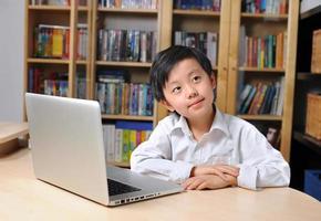 rapaz asiático na frente do computador portátil foto