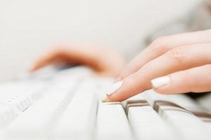 mãos femininas digitando no teclado do viajante foto