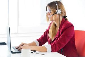 garota de negócios jovem usando seu computador. foto