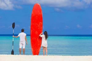 jovem casal com prancha vermelha na praia branca foto