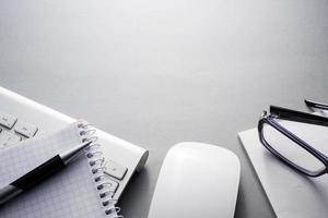 teclado, mouse e material de escritório na mesa cinza