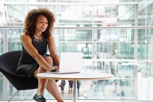 jovem empresária usando computador portátil no interior moderno foto