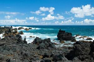 rochas do vulcão na praia em hana maui havaí foto