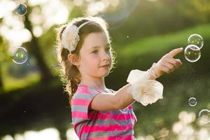 linda garota perseguindo bolhas de sabão foto