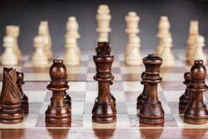 tabuleiro de xadrez com figuras na mesa de madeira foto