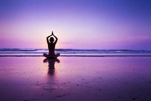 mulher praticando ioga na praia foto
