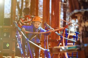 menino subindo no parque de atividades de aventura foto