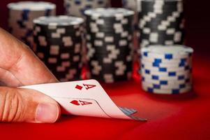 jogo de pôquer. mão do homem com um par de ases foto