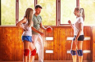 treinador e alunos no treinamento de vôlei foto