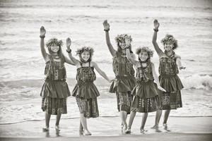 cinco meninas hula na beira da água na praia foto