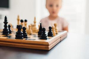 pequeno jogador de xadrez pensando em segundo plano foto