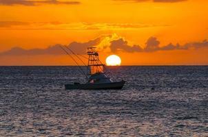 belo pôr do sol por trás do barco de pesca esportiva em maui, Havaí, EUA foto