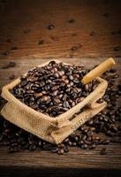grão de café dentro saco e colher de madeira no bloco de madeira foto