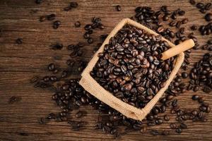 grão de café dentro saco e colher de madeira no bloco de madeira