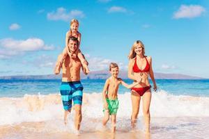 família feliz se divertindo na praia foto