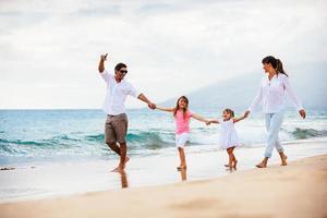 família jovem feliz caminhando na praia foto