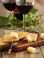 queijo e bolachas com copos de vinho tinto