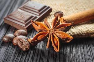 barra de chocolate e especiarias na mesa de madeira foto