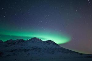 aurora boreal atrás de uma montanha
