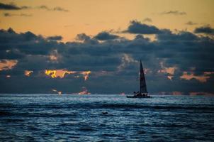 silhueta de veleiro ao pôr do sol foto