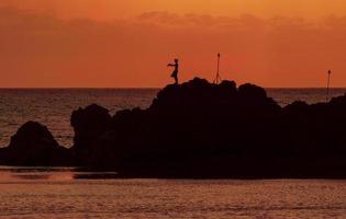 mergulhador de penhasco havaiano contra um pôr do sol laranja foto