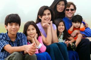 família multirracial, sentado na praia