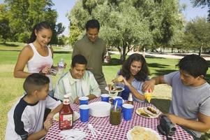 família reunida em torno da mesa de piquenique foto