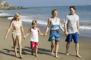 família de mãos dadas na praia