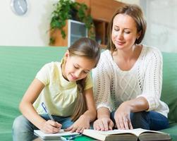mãe com filha fazendo lição de casa foto