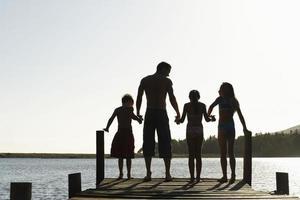 família em pé na beira do cais foto