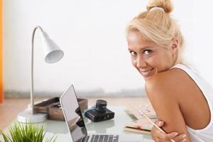 mulher loira com olhar sensual. ela está no seu local de trabalho foto