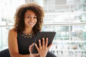 jovem empresária usando computador tablet no interior moderno