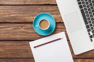 xícara de café e papel com computador portátil foto