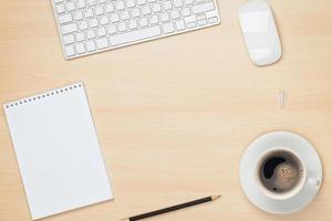 mesa de escritório com bloco de notas, computador e xícara de café foto