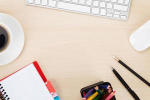 mesa de escritório com computador, suprimentos e xícara de café foto
