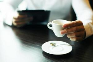 xícara de café na mão. computador tablet turva foto