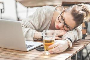 garota cansada com cerveja e computador em Londres foto