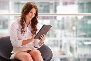 jovem empresária usando computador tablet no interior moderno foto
