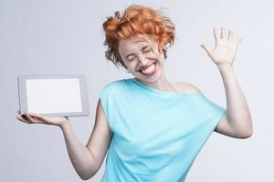 garota ruiva emocional, segurando um computador tablet foto