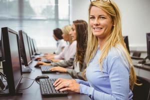 mulher feliz na sala de informática, sorrindo para a câmera foto