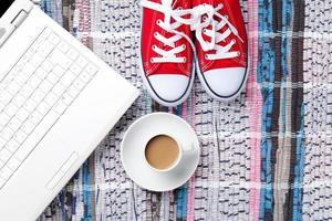 xícara de cappuccino perto de sapatos desportivos vermelhos e computador foto