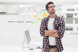 empresário pensativo com braços cruzados em pé foto