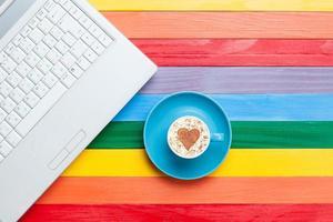 xícara de cappuccino com forma de coração e computador foto