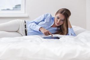 mulher bonita usando computador tablet na cama dela foto