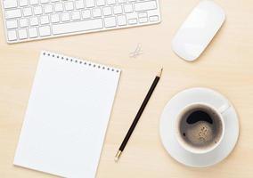 mesa de escritório com bloco de notas, computador e xícara de café
