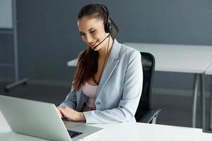 operador de call center sentado na frente do computador foto