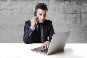 feche a imagem do homem de negócios multitarefa usando um laptop foto