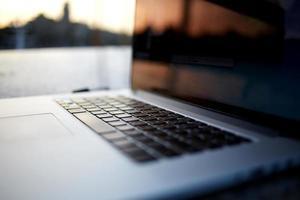 imagem recortada de net-book aberto, deitado sobre uma mesa ao ar livre foto