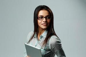 jovem alegre usando óculos, segurando o computador da tabuleta foto